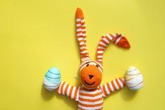 复活节兔子和鸡蛋在黄色背景 库存照片