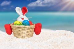 复活节兔子用在一个热带海滩的色的鸡蛋 免版税库存照片