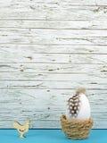 复活节在蓝色的背景用复活节彩蛋和公鸡在木头前面 免版税库存照片