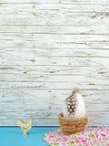 复活节在蓝色的背景用复活节彩蛋和公鸡在木头前面 库存图片