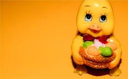 复活节小鸡的逗人喜爱的蜡烛在淡桔色的背景的 免版税库存照片
