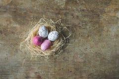 复活节巢的关闭和顶视图用在木背景的白色和桃红色有雀斑的复活节彩蛋 免版税库存图片