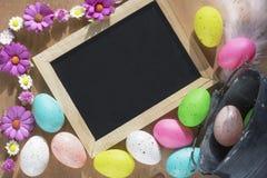 复活节彩蛋和一个黑板有花的 免版税库存图片