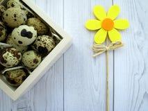 复活节彩蛋和一朵黄色花在一张白色木桌上 免版税库存照片