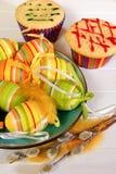 复活节彩蛋和两块杯形蛋糕 免版税库存图片