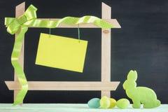 复活节彩蛋和兔宝宝与框架和纸笔记 免版税库存照片