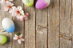 复活节彩蛋和杏仁在老木桌上开花 库存图片