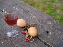 复活节彩蛋和杯在桌上的红酒 免版税库存照片