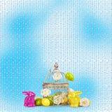 复活节彩蛋和滑稽的兔宝宝在蓝色背景 免版税库存图片