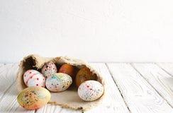 复活节彩蛋在轻的背景的帆布织品包裹了 免版税库存图片