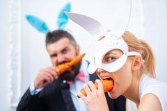 复活节彩蛋夫妇 微笑复活节 吃红萝卜的逗人喜爱的小兔 复活节兔子吃红萝卜 库存图片