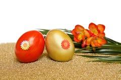 复活节彩蛋开花小苍兰金黄红色 免版税库存照片