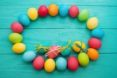 复活节彩蛋框架在蓝色木背景的 顶视图和拷贝空间 嘲笑 4月假日 食物鸡蛋 库存图片