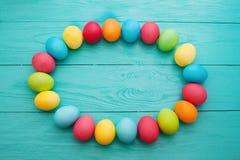 复活节彩蛋框架在蓝色木背景的 顶视图和拷贝空间 嘲笑 4月假日 食物鸡蛋 图库摄影