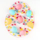复活节彩蛋概念 五颜六色的鸡蛋和糖果与桃红色缎带在被隔绝的白色背景 平的位置 免版税图库摄影