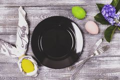复活节彩蛋的顶视图在餐巾包裹了以兔子耳朵、一个黑色的盘子和利器,在a的五颜六色的复活节彩蛋的形式 免版税库存图片