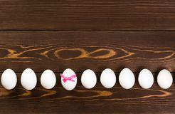 复活节彩蛋线在木背景 其中一个鸡蛋有一把桃红色弓 免版税库存照片