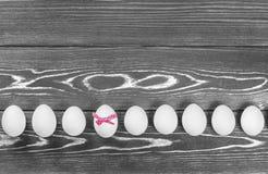复活节彩蛋线的黑白照片在木背景 其中一个鸡蛋有一把桃红色弓 库存照片