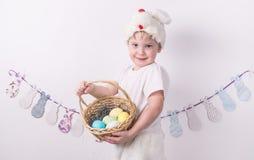 复活节快乐的祝贺:一只复活节兔子的服装的男孩与篮子和鸡蛋的 免版税库存照片