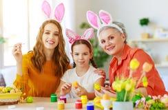 复活节快乐!家庭祖母、母亲和孩子绘鸡蛋并且为假日做准备 免版税库存照片