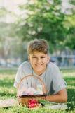 复活节快乐!蓝色衬衣的逗人喜爱的微笑的男孩少年在春天公园拿着篮子用在草的手工制造色的鸡蛋 库存图片