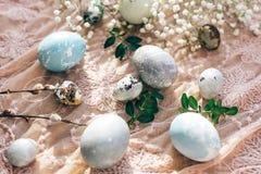 复活节快乐,季节问候 时髦的复活节彩蛋平展放置与春天花和杨柳分支在晴朗的土气织品 图库摄影