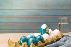复活节快乐,站立在白色颜色鸡蛋的有机蓝色复活节彩蛋等待绘画,复活节假日装饰 库存图片