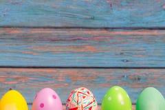 复活节快乐,站立有蓝色木背景,复活节假日与拷贝空间的装饰概念的五颜六色的复活节彩蛋 免版税库存照片