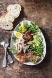 复活节早午餐-煮沸的鸡,鲕梨,鸡蛋,芝麻菜, kumato蕃茄,在木棕色背景的烟肉沙拉 图库摄影
