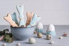 复活节春天装饰构成用以一只滑稽的兔子的形式自创复活节曲奇饼,鹌鹑蛋 在一灰色concre 库存照片