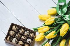 复活节春天装饰构成 绿色丝带和一点箱子栓的黄色郁金香花束用鹌鹑蛋 关闭portr 库存图片