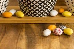 复活节木表面上的糖果鸡蛋除与有bla的碗以外 免版税库存图片