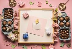 复活节构成用朱古力蛋、春天花、各种各样的装饰、木兔子和鸟,在桃红色后面的小礼物 免版税库存照片