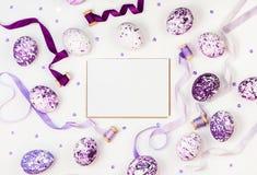 复活节构成用淡紫色大理石鸡蛋、衣服饰物之小金属片和丝绸丝带在白色背景 问候文本的空间 免版税库存照片