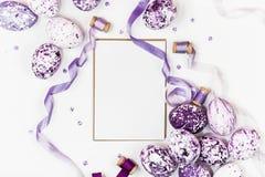 复活节构成用紫色大理石鸡蛋、衣服饰物之小金属片和丝绸丝带在白色背景 问候文本的空间 免版税库存图片