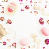 复活节桃红色框架怂恿与麻线,玫瑰开花和在白色背景,顶视图,油脂位置的磁带 背景美丽的复活节彩蛋节假日污点 库存照片