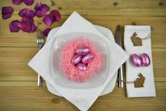 复活节桌在白色的餐位餐具与手工制造桃红色巢和发光的朱古力蛋与木小兔装饰 库存图片