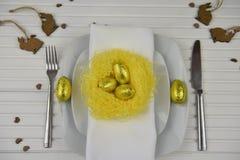 复活节桌在白色的餐位餐具与黄色手工制造巢和金黄颜色怂恿与木小兔装饰 免版税图库摄影