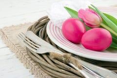 复活节正餐设置用二桃红色鸡蛋和郁金香 免版税库存照片