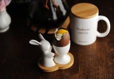 复活节点心朱古力蛋充满奶油色仿效白色和卵黄质 服务在与复活节兔子的持有人 免版税库存照片