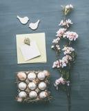 复活节组成与蛋、开花和空插件嘲笑的问候布局在灰色背景 库存照片