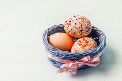 复活节绘了在蓝色的鸡蛋柳条筐 库存图片