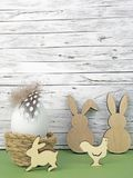 复活节背景用复活节彩蛋、复活节兔子和公鸡在绿色在木头前面 库存图片