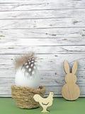 复活节背景用复活节彩蛋、复活节兔子和公鸡在绿色在木头前面 免版税图库摄影