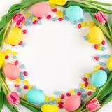 复活节花圈由黄色郁金香、五颜六色的鸡蛋和糖果制成在白色背景 r 免版税库存图片