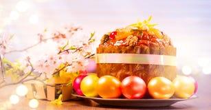 复活节蛋糕和五颜六色的被绘的鸡蛋 在白色背景的传统复活节假日食物边界设计 Panetone 免版税库存图片