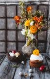 复活节蛋糕用复活节彩蛋在巢和春天在水罐开花 免版税库存图片
