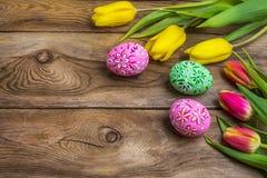 复活节问候用鸡蛋和黄色红色郁金香 免版税图库摄影