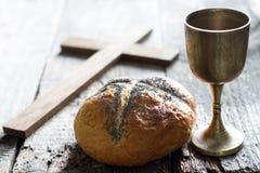 复活节面包酒和十字架在葡萄酒老木背景 库存照片