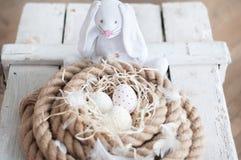 复活节,鸡蛋,鸡怂恿,鹌鹑蛋,鸡蛋,绳索,巢,白色,羽毛,在干草,白色兔子,复活节兔子 免版税图库摄影